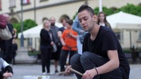 O baterista da rua executa em uma cubeta e em pratos na frente da audiência dos povos filme