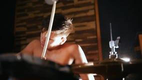 O baterista descamisado joga a música com uma paixão no estúdio Fim acima filme