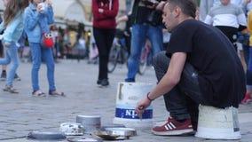 O baterista executa em uma cubeta simples e em pratos na rua na frente da audiência dos povos filme