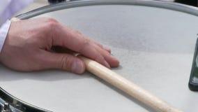 O baterista joga com varas em um cilindro de cilada Um homem guarda um pilão em sua mão e bate no cilindro filme