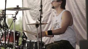 O baterista joga a música ao ensaiar uma música em um grupo de rock do oncert video estoque