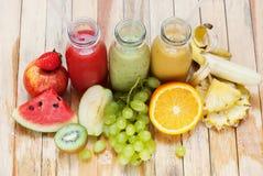 O batido dos sucos da fileira engarrafa o fruto alaranjado verde vermelho imagem de stock royalty free