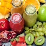 O batido fresco engarrafa frutos alaranjados verdes vermelhos imagens de stock royalty free
