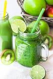 O batido vegetal verde fresco na caneca do frasco, suco de fruto na garrafa, dispersou maçãs, cal, quivi Imagem de Stock