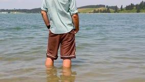 O Bavarian refrigera seus pés em um lago vídeos de arquivo