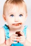 O bebé come o chocolate Imagem de Stock