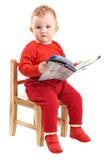 O bebé vestiu-se no assento vermelho na leitura da cadeira Fotografia de Stock