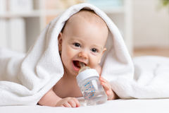 O bebê adorável bebe a água da garrafa envolvida Fotos de Stock Royalty Free