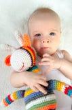 O bebê adorável que joga com feito à mão colorido faz crochê o brinquedo fotografia de stock