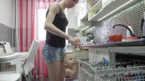 O bebê ajuda a mãe a esvaziar na vida real uma máquina de lavar louça, estilo de vida ocasional interior vídeos de arquivo