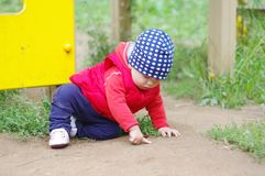 O bebê aponta algo que senta-se na terra Imagens de Stock Royalty Free