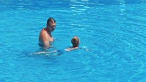 O bebê aprende flutuar na água vídeos de arquivo