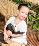 o bebê asiático de sorriso abraça o cão preto pequeno no braço Fotografia de Stock Royalty Free