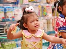 O bebê asiático pequeno aprecia estar em um carrinho de compras que espera sua mãe para fazer a compra foto de stock royalty free