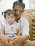 O bebê asiático que olha seu ` s da mãe entrega o fruto da casca, pomelo foto de stock