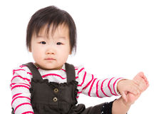 O bebê asiático toca em seu pé Fotos de Stock