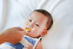 O bebê asiático toma o xarope da medicina de uma colher Criança doente imagens de stock