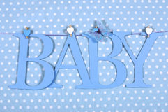 O BEBÊ azul do berçário do bebê rotula a estamenha que pendura dos Pegs em uma linha contra um fundo azul do às bolinhas imagens de stock royalty free