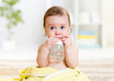 O bebê bebe a água da garrafa que senta-se com toalha Foto de Stock