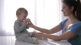 O bebê bonito com os rasgos nos olhos que bebe a água pura do vidro das mãos da mãe e exulta em extinguir da sede dentro filme