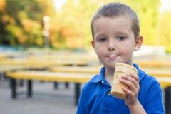 O bebê bonito, come o gelado Uma criança come o gelado fora imagens de stock