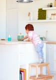 O bebê bonito da criança escala no tamborete da etapa, tentando alcançar coisas na mesa alta na cozinha Fotografia de Stock