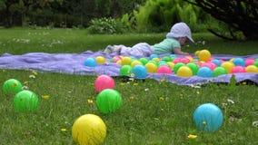 O bebê bonito do borrão tem o divertimento entre bolas coloridas na manta no prado 4K video estoque