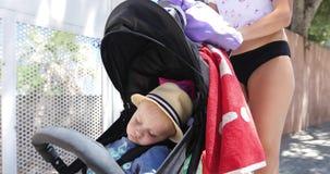 O bebê bonito está dormindo no carrinho de criança em férias filme