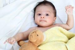 O bebê bonito está feliz com o urso amarelo da cobertura e da boneca Imagens de Stock Royalty Free