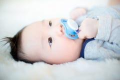 O bebê bonito está sugando a chupeta e está dormindo em um tapete branco macio fotografia de stock