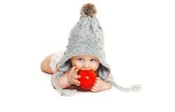 O bebê bonito morde a maçã vermelha no chapéu feito malha cinza no branco Fotos de Stock Royalty Free