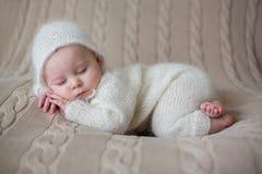 O bebê bonito no branco fez malha os panos e o chapéu, dormindo foto de stock