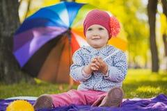 O bebê bonito no parque verde olha a câmera imagem de stock