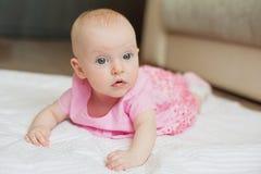 O bebê bonito no vestido cor-de-rosa encontra-se no backgroun branco Criança recém-nascida no interior da casa Fotos de Stock