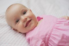 O bebê bonito no vestido cor-de-rosa encontra-se no backgroun branco Retrato do close-up, bebê de sorriso Imagens de Stock