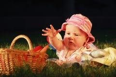 O bebê bonito olha na cesta com vegetais Fotografia de Stock