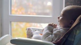 O bebê bonito olha para fora a janela