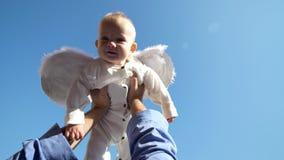 O bebê bonito pequeno com as asas brancas do anjo rised acima nas mãos do pai ao céu azul filme