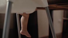 O bebê bonito senta-se em uma cadeira das crianças altas e move-se seus pés O bebê levanta um pé filme