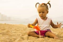O bebê bonito senta-se enfrentando a câmera e jogando com o ancinho do brinquedo na areia na praia Fotos de Stock Royalty Free