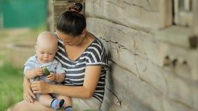 O bebê bonito senta-se no mum nas mãos e come-se o pepino Perto de uma casa de madeira velha vídeos de arquivo