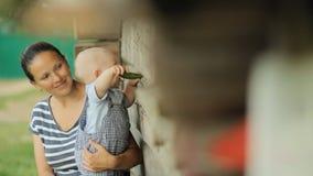 O bebê bonito senta-se no mum nas mãos e come-se o pepino Perto de uma casa de madeira velha filme