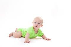 O bebê bonito surpreendido que encontra-se em seu estômago e que olha veio foto de stock