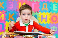 O bebê bonito tira um lápis no álbum Fotos de Stock Royalty Free
