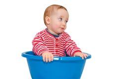O bebê bonito vestiu-se e senta-se em uma bacia azul Foto de Stock
