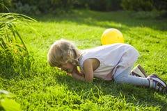 O bebê caiu e gritos em uma grama em um jardim imagem de stock