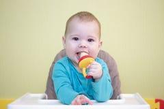 O bebê caucasiano 5 da criança 6 meses de menina do menino senta-se em uma cadeira alta e come-se o fruto de um nibbler a criança foto de stock royalty free