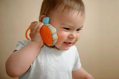 O bebê caucasiano novo que fala em um espaço da cópia do telefone celular do brinquedo, fecha-se acima do retrato foto de stock royalty free