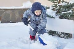 O bebê caucasiano pequeno bonito trabalha com pá a neve na jarda com o abeto no fundo Ar livre do inverno, sorrindo, mordentes co imagens de stock