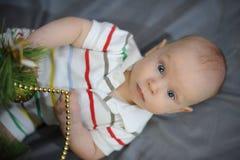 O bebê com olhos azuis aproxima a árvore de Natal Ano novo imagens de stock